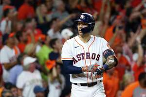 Houston Astros shortstop Carlos Correa (1) points to his wrist after hitting a solo home run to give the Astros a 4-3 lead during the seventh inning in Game 1 of the American League Championship Series on Friday, Oct. 15, 2021, at Minute Maid Park in Houston.