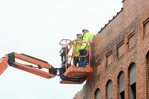 Workers with Shireman Farms Excavating remove bricks Friday from a building after a roof collapsed Tuesday at 102½ and 104 N. West St., which is on the east side of the street across from Morgan County Courthouse to the west. For safety reasons, the street has been closed to the public until further notice.