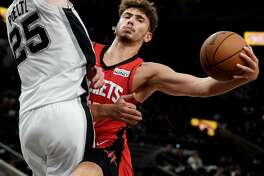 Houston Rockets' Alperen Sengun, right, looks to pass as he is defended by San Antonio Spurs' Jakob Poeltl during the first half of a preseason NBA basketball game, Friday, Oct. 15, 2021, in San Antonio. (AP Photo/Darren Abate)