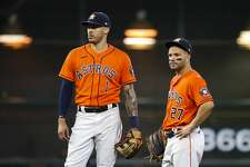 Houston Astros shortstop Carlos Correa (1) and Houston Astros second baseman Jose Altuve (27) wait during a pitching change during the second inning in Game 2 of the American League Championship Series on Saturday, Oct. 16, 2021, at Minute Maid Park in Houston.