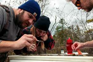 Jonathan Alfano, Rebecca Herd and Josh Shields collect specimens from a bucket of water they collected in order to determine the health of the rived during a stream sampling event at the Little Manistee River on Saturday. The number of pollution sensitive organisms found in a sample can determine the health of the river.The stream sampling event, which is put on by the Manistee Conservation District occurs in May and October. The event has been going on since 2016.
