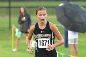 Father McGivney freshman Elena Rybak runs alone on the lead near the finish in her Madison County Meet victory at the Bethalto Sports Complex.