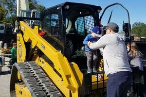 Dad helps Calvin Thompson (2 1/2) out of some construction equipment.