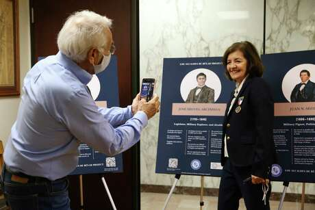 Descendant of Jose Miguel Arciniega, Norma Arciniega Langwell, gets her photo taken by historian Andres Tijerina in the Spanish Bexar Archives at the Bexar County Clerk's Office on Wednesday, Oct. 6. Jose Miguel Arciniega served as mayor of San Antonio in 1830 and again in 1833. His portrait is one of five that are part of Los Alcaldes de Bexar exhibition, in honor of Hispanic Heritage Month, at the archives. Members of San Antonio Barrio Girls and Ghost Town Survivors were present during the presentation by various historians. The nonprofit Los Alcaldes de Bexar is working on creating forensic portraits of San Antonio mayors that served before the republic. Five such portraits have been created out of 105 on the list that dates between 1731 and 1836.