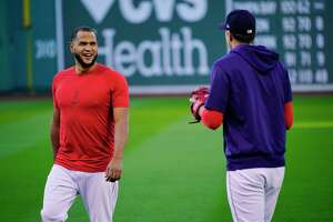 Boston Red Sox Game 3 starting pitcher Eduardo Rodríguez chats with teammate Nick Pivetta at a baseball practice at Fenway Park, Sunday, Oct. 17, 2021, in Boston. The Red Sox host the Houston Astros on Monday night. (AP Photo/Robert F. Bukaty)