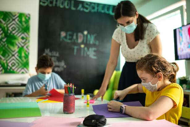 School children and female teacher with protective face masks on art class at private school classroom