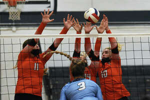 Edwardsville's Gabby Saye, left, Sydney Harris, center, and Emma Garner try to block an attack from Mater Dei's Tori Mohesky in the first set.
