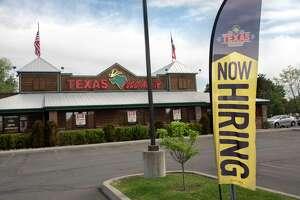 "A banner advertising ""now hiring"" is seen outside Texas Roadhouse restaurant on Friday, June 4, 2021 in Colonie, N.Y. (Lori Van Buren/Times Union)"
