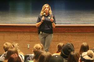 Carly Pitrago, Michigan State Police detective, talks to students about cyber safety in the Manistee Middle High School auditorium on Monday. Pitrago and digital forensic analyst Craig Baumgartner gave five age-adjusted presentations to MMHS students.