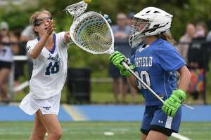 Ludlowe goalie Kennedy Carr (00) picks the ball out of the air in front of Darien's Ceci Stein (16) during the CIAC Class L girls lacrosse final at Bunnell in Stratford on Saturday, June 12, 2021.