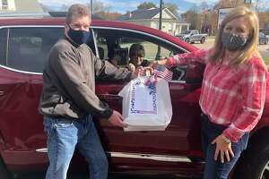 Main Street Community Center board members Kevin Doak, left, and Sarah Goldammer provide a meal for a veteran during last year's Veterans Luncheon at the center. This year's event, which is curbside pickup or delivery only, is scheduled for Thursday, Nov. 4.