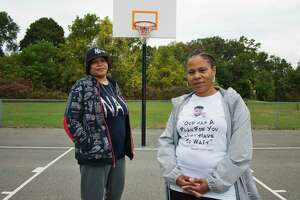 Ebony Banks, left, the aunt of Naylon Carrington, and Sondra Banks, Carrington's mother, stand under a basket at the Central Park basketball courts on Monday, Oct. 18, 2021, in Schenectady, N.Y. Carrington was killed last October in a motor vehicle crash. Sondra and Ebony are posing at what they said was Naylon's favorite basket at the court.