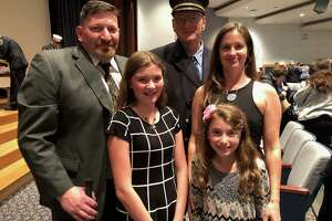 """Shelton firefighter David Collins, with his family - Peter and Michelle and granddaughters Dana and Julia - presented the Dolores """"Dolly"""" Collins Award to firefighter Michael Kellett at the fire department awards ceremony Oct. 16."""
