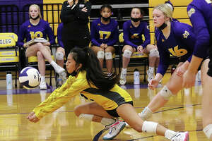 CM libero Ella Middleton (left) goes down to receive a serve in front of teammate Emily Williams (16) during the second set against Mascoutah on Tuesday night in Bethalto.