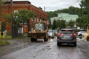 Traffic weaves around abandoned vehicles in South Norwalk following the rains of Tropical Storm Ida.