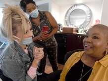 """Madison Sipes and Karen Fillyaw look on as Charmayne Hadnot reacts to her new look during """"Brave and Beautiful"""" - a make-over day for breast cancer patients and survivors at the Holiday Inn on Walden Road. Photo made Thursday, September 23, 2021 Kim Brent/The Enterprise"""