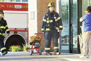 A woman, who was soon transported to a local hospital, coughs into her hands as firefighters bring exhaust fans into the Hampton Inn and Suites early Wednesday to investigate a report of smoke in a fourth floor room of the hotel. The smoke was determined to be aerosol mist from a bug bomb according to fire officials. Two women were transported to the hospital showing signs of smoke inhalation.