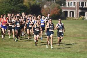 A pack of runners, led by Staples' Zachary Taubman (816), Ludlowe's Nathan Cramer (816) and Trumbull's Mohammed Abunar (860), come down the first hill during the FCIAC boys cross country championship in New Canaan's waveny Park on Wednesday, Oct. 20, 2021.