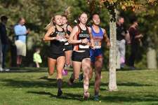 Ridgefield's Katie Rector (center), Danbury's Stephanie Queiroz (right) and Trumbull's Kali Holden (left) lead the way down a hill during the FCIAC girls cross country championship in New Canaan's Waveny Park on Wednesday, Oct. 20, 2021.