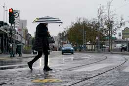 A pedestrian carries an umbrella while crossing a street at Fisherman's Wharf in San Francisco, Wednesday, Oct. 20, 2021. Showers drifted across the drought-stricken and fire-scarred landscape of Northern California on Wednesday, trailed by a series of progressively stronger storms that are expected to bring significant rain and snow into next week, forecasters said.