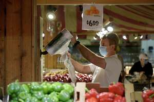 Christian Rogg, of New Milford, reaches for a plastic bag while shopping at Stew Leonard's . The mask mandate for the city of Danbury has been lifted. While Stew Leonard's still requires its employees to wear masks shopper are no longer required to do so. Wednesday, October 20, 2021, in Danbury, Conn.
