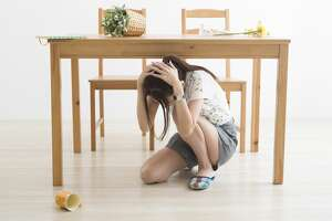 A woman takes cover under a table during an earthquake.
