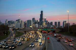 Traffic on the Kennedy Expressway in Chicago at dusk, with the downtown skyline behind.