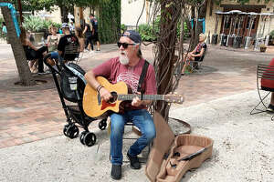 Edwardsville musician Butch Moore does some street playing during a visit to the Pearl District in San Antonio, Texas.