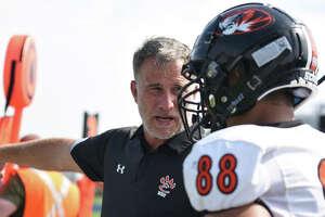 Edwardsville coach Matt Martin talks to Iose Epenesa on the sideline during a game against Belleville East in Belleville.