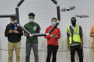 Students, Jude Larsen, left, a senior from Troy, Drevan Seyay, second from left, a senior from Troy, Leo Platti, third from left, a senior from Hudson, practice flying drones at the UAlbany Drone Lab, as UAlbany student, Edens Michel, who is studying in the Informatics department at the college, looks on, on Thursday, Oct. 21, 2021, in Albany, N.Y. The high school students are studying in the New Visions Questar EPICH (Emergency Preparedness, Informatics, Homeland Security and Cyber Security) program. The Questar EPICH program is partnering with UAlbany College of Emergency Preparedness, Homeland Security and Cyber Security to begin to prepare high school students for careers in homeland security.