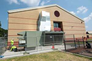 """Workers from KMK Insulation of North Haven, finish working on the new DOAS system, or """"dedicated outdoor air system,"""" at Westover Elementary School in Stamford, Conn., on Friday August 27, 2021. The third and final unit was installed in October."""