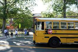 A school bus picks up students during dismissal at Old Greenwich School in Old Greenwich, Conn. Wednesday, Sept. 23, 2020.