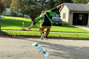 Andrew Hirschberger performs a skateboard trick on Silver Street in Bad Axe. A father and son are working to bring a skatepark to Bad Axe, and they'll need the public's support to do it. (Mark Birdsall/Huron Daily Tribune)