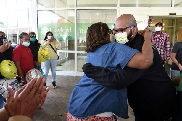 Fannie Hardy (center) of Hamden hugs her grandson, Glenn Merritt, III, upon his release from Gaylord Hospital in Wallingford after rehabilitation from COVID-19 on October 22, 2021.