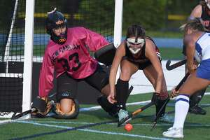 New Canaan goalie Grace Gilman and Keira Cooney (12) defend the cage against Darien on Friday.