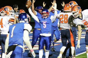 Carlinville RB Mason Patton (5) signals touchdown in front of two Cavaliers linemen before celebrating with WR Ethen Siglock (1) after scoring a go-ahead TD in the fourth quarter Friday night at Carlinville. Pana answered with two TDs to win 27-13 and complete a 9-0 regular-season and SCC championship.