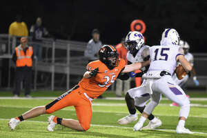 Edwardsville defensive end Carson Forsting attempts to bring down CBC quarterback Patrick Heitert for a sack during the first quarter.