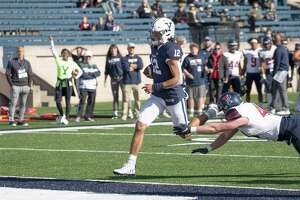 Yale quarterback Nolan Grooms scores his second touchdown against Penn on Saturday on a 4-yard run.