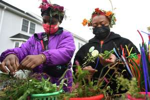 Ssica Lucien-Benoit, left, and Vetiveah Harrison, both of Bridgeport, create flower crowns at the 2021 Harvest Fest at the Reservoir Community Farm in Bridgeport, Conn. on Saturday, October 23, 2021.