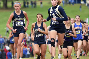Father McGivney's Elena Rybak, left, and Katelyn Hatley, center, make their way up the hill at the start of the Class 1A Belleville Althoff Regional.
