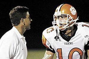 Former Edwardsville coach Tim Dougherty, left, talks to EHS quarterback Joe Allaria during a game in 2006.