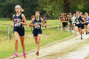 Father McGivney's Elena Rybak (left) and Kaitlyn Hatley lead the field early in the race Saturday morning at the Belleville Althoff Class 1A Regional girls cross country meet at Clinton Hills Conservation Park in Swansea. Rybak won the race, with Hatley placing second.