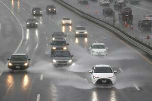 Cars drive through a flooded section of Highway 101on Oct. 24, 2021 in Corte Madera. A Category 5 atmospheric river is bringing heavy precipitation, high winds and power outages to the San Francisco Bay Area. The storm is expected to bring anywhere between 2 to 5 inches of rain to many parts of the area.