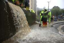 Workers try to divert water into drains as rain pours down on October 24, 2021 in Marin City, California.
