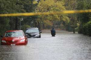 A pedestrian walks on a flooded street on October 24, 2021 in Kentfield, California.
