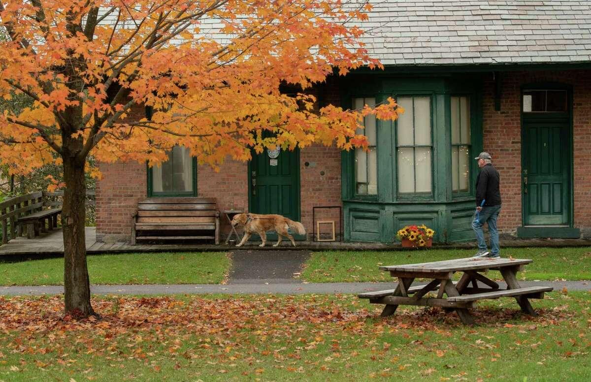 A man walks a dog at Lions Park on Monday, Oct, 25, 2021 in Niskayuna, N.Y.