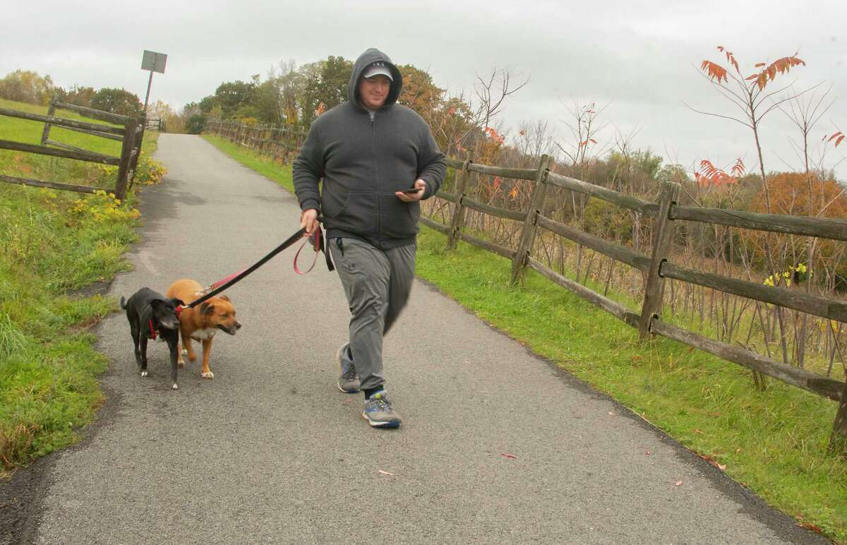Jared Seastrum of Latham walks his dogs Hannah, left, and Ellie along the Mohawk-Hudson Bike Trail on Monday, Oct, 25, 2021 in Niskayuna, N.Y.