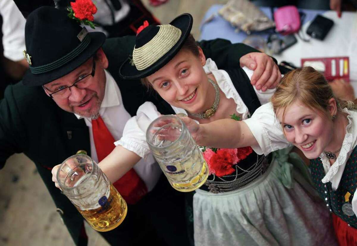 MUNICH, GERMANY - SEPTEMBER 19: The visitors in traditional Bavarian outfit toast with beer mugs during the second day of the Oktoberfest on September 19, 2010 in Munich, Germany. 2010 marks the 200th anniversary of Oktoberfest.The Oktoberfest tradition started in 1810 to celebrate the October 12th marriage of Bavarian Crown Prince Ludwig to the Saxon-Hildburghausen Princess Therese. The citizens of Munich were invited to join in the festivities which were held over five days on the fields in front of the city gates. The main event of the original Oktoberfest was a horse race. The world's biggest beer festival will last this year from September 18 to October 4. (Photo by Alexandra Beier/Getty Images)