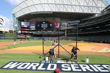Members of the grounds crew paint the World Series logo on the field during workouts ahead of Game 1 of the World Series at Minute Maid Park, Monday, Oct. 25, 2021 in Houston.