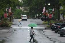 Folks take cover from the rain as Tropical Storm Henri hits Greenwich, Conn. Sunday, Aug. 22, 2021.